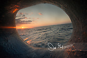 Sunset over the ocean, viewed through a porthole on a ship.