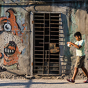 A boy carries lunch on the street past a doorway and crumbling wall mural of a monster in Havana, Cuba.