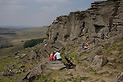 Climbing familes and gritstone geology on Long Causeway cliffs, Peak District National Park, Derbyshire...Located in the Peak District National Park in England Stanage Edge is the largest of the gritstone edges that overlook Hathersage in Derbyshire. Stanage Edge at approximately 4 miles in length and 458m at its highest point is the largest of the gritstone cliffs that overlook Hathersage, Derbyshire. The area is one of the most popular locations in the Peak District National Park for climbing and walking with hundreds of rock climbing routes to challenge all ranges of ability. Walkers are drawn to the area to enjoy the varied moorland scenery with stunning views across the surrounding countryside including Hathersage, Castleton and the 'Shivering Mountain', Mam Tor in the west. A walk along the edge is an easy route but the exposed cliff can make conditions difficult throughout the year as it is often battered by wind, rain and regular snowfall in the winter months. There are a number of popular walks including routes along the remains of a Roman Road and towards Redmires Reservoir to the east as well as longer walks such as those including the nearby Longshaw Estate. Sopurce http://www.stanageedge.co.uk