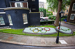 © licensed to London News Pictures. London, UK 16/07/2012. A flower arrangemant in the shape of the The Olympic Rings in the garden at the front of Downing Street in London on July 16, 2012. The flowers were grown by Royal Parks and planted by Downing Street gardeners Paul Schooling and Guillaume Tremorin. Photo credit: Tolga Akmen/LNP