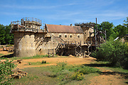 North Range or Logis Seigneurial in the centre, completed 2010, with Corner Tower and Chapel Tower on the left and Great Tower or Tour Maitresse on the right, still under construction, and lifting gear or squirrel cage with double drum, at the Chateau de Guedelon, a castle built since 1997 using only medieval materials and processes, photographed in 2017, in Treigny, Yonne, Burgundy, France. The Guedelon project was begun in 1997 by Michel Guyot, owner of the nearby Chateau de Saint-Fargeau, with architect Jacques Moulin. It is an educational and scientific project with the aim of understanding medieval building techniques and the chateau should be completed in the 2020s. Picture by Manuel Cohen