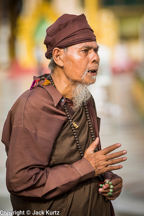07 JUNE 2014 - YANGON, YANGON REGION, MYANMAR: A Burmese hermit monk walks around Shwedagon Pagoda in Yangon. Shwedagon Pagoda is officially called Shwedagon Zedi Daw and is also known as the Great Dagon Pagoda and the Golden Pagoda. It's a 99 metres (325 ft) gilded pagoda and stupa located in Yangon. It is the most sacred Buddhist pagoda in Myanmar with relics of the past four Buddhas enshrined within: the staff of Kakusandha, the water filter of Koṇāgamana, a piece of the robe of Kassapa and eight strands of hair from Gautama, the historical Buddha.   PHOTO BY JACK KURTZ