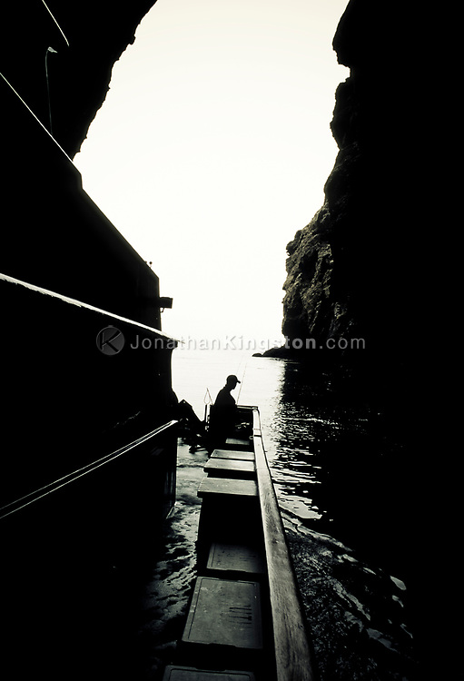 Silhouette of a man with a baseball cap standing next to fishing rods on the stern of a large boat inside a sea cave, Channel Islands National Park, California.  Painted Cave is one of the largest and deepest sea caves in the world and is found on the northwest coastline of Santa Cruz Island.  Named because of its colorful rock types, lichens, and algaes, Painted Cave is nearly a quarter-mile long and 100 feet wide, with an entrance ceiling of 160 feet and a waterfall over this entrance in the spring.