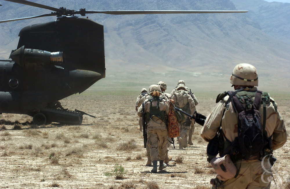 U.S. Army troops board a CH-47 Chinook helicopter during a mission to clear debris June 20, 2002 from the Bagram air base in Afghanistan.  Bagram, a former Soviet military base is littered with hundreds of wrecked vehicles and airplanes along with thousands of unexploded ordinance left over from the Soviet occupation of Afghanistan.