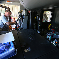 Chris Estes, left, puts a fresh air tank into the passenger seat of their new truck so it will be ready for their next call.