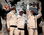 14FEB10 The 33rd America's Cup, Valencia, Spain..BMW Oracle Racing win the America's Cup 2010. .left to right, Skipper / Helmsman James Spithill; CEO of BMW Oracle Racing Russell Coutts; CEO of Oracle Larry Ellison; Eliison lifts the America's Cup in their win over Alinghi, to take the Cup back to the San Fransisco's Golden Gate Yacht Club.