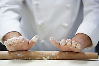 Chef rolling dough using rollingpin close-up