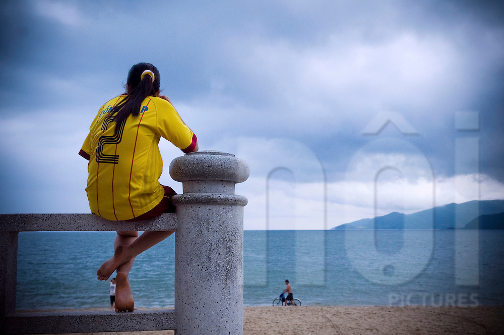 A young Vietnamese girl wearing a soccer jersey sits on a railing by Nha Trang beach and looks out over the sea, Vietnam, Southeast Asia