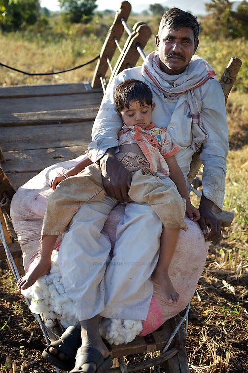 A boy takes an afternoon sleep on the lap of a cotton-farmer close to the village of Chitalwadi in the Vidarbha region of Maharashtra...Photo: Tom Pietrasik.January 2011.Maharashtra, India