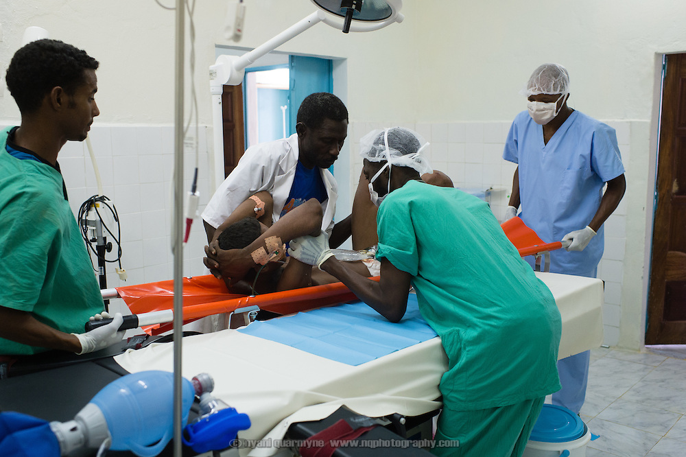 A gunshot victim is transferred to the operating table at the recently completed Médecins Sans Frontières (MSF) surgical unit in Bassikounou, Mauritania on 10 March 2013. Gunshot injuries are rarely seen at the unit - the victim was shot in Mali, and traveled through the night to reach the unit Bassikounou, which was the closest surgical facility.