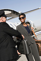 Mid-adult businesswoman giving suitcase to chauffeur in front of airplane