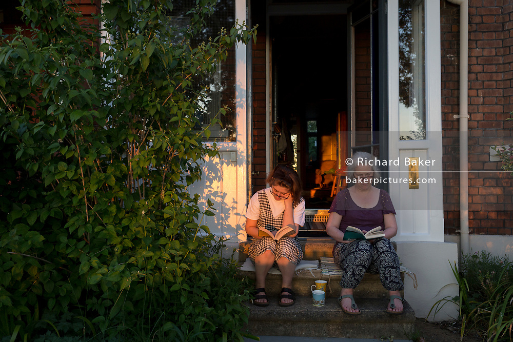 The number of UK deaths from Coronavirus, a further 363 victims taking the total to 35,704, coincided with the hottest day of the year so far, with 27.8 degrees recorded at Heathrow Airport, and a mother and daughter read their books on the steps of their home's porch in late sunshine while still under the UK government's lockdown rules of social distancing - during a warm evening in Lambeth, south London, on 20th May 2020, in London, England.