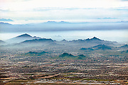 Smog settles between hills north of downtown Phoenix. In the Phoenix metropolitan area,  the natural inversion layer traps rising particulates and forms 'brown cloud' as the ground heats up during the day.  Smog impacts inhabitants of urban populations that already suffer from respiratory ailments, and continued suburban growth contributes to declining air quality.