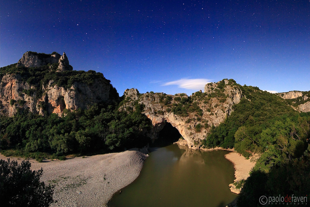 "A view on a clear, starry night of Pont d'Arc, a beautiful natural stone bridge the Ardeche river dug in the cliff. It is placed right at the beginning of the canyons, just off the nice small town of Vallon Pont d'Arc.<br /> The full moon was so bright that night that I blew off my first attempts at 1 minute f4. This is a sequence of 5 vertical frames all exposed for 30"" at f5, and then stitched together in Photoshop."