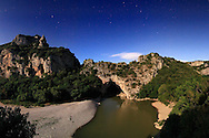 A view on a clear, starry night of Pont d'Arc, a beautiful natural stone bridge the Ardeche river dug in the cliff. It is placed right at the beginning of the canyons, just off the nice small town of Vallon Pont d'Arc.<br /> The full moon was so bright that night that I blew off my first attempts at 1 minute f4. This is a sequence of 5 vertical frames all exposed for 30&quot; at f5, and then stitched together in Photoshop.