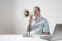 Businessman sitting at desk speaking through megaphone
