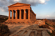 Low angle view of the Temple of Concord, 5th century BC, Agrigento, Sicily, Italy,  pictured on September 11, 2009, in the warm evening light. In the foreground the Paleochristian Necropolis can be seen. Well preserved owing to its 6th century AD conversion to a church, the Temple of Concord is a typical example of optical correction whose tapering columns create the illusion of a perfectly aligned building. Its frieze consists of alternating triglyphs and metopes, and the pediment is undecorated. The Valley of the Temples is a UNESCO World Heritage Site. Picture by Manuel Cohen.