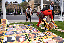 © Licensed to London News Pictures. 14/05/2018. London, UK. People lay out photographs of the 71 victims of the Grenfell Tower fire at a protest in Parliament Square to mark eleven months since the tragedy. Photo credit: Rob Pinney/LNP