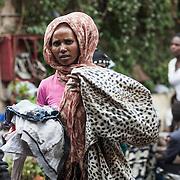 Quasi 800 profughi di cui più di 100 bambini vengono ospitati nella struttura di accoglienza Baobab di Via Cupa a Roma. La struttura può accogliere circa 220 migranti. Semplici cittadini e il gruppo SEL hanno raccolto generi alimentari da distribuire agli all'interno della struttura. Una donna nel cortile del centro Baobab con in mano teli ed indumenti.