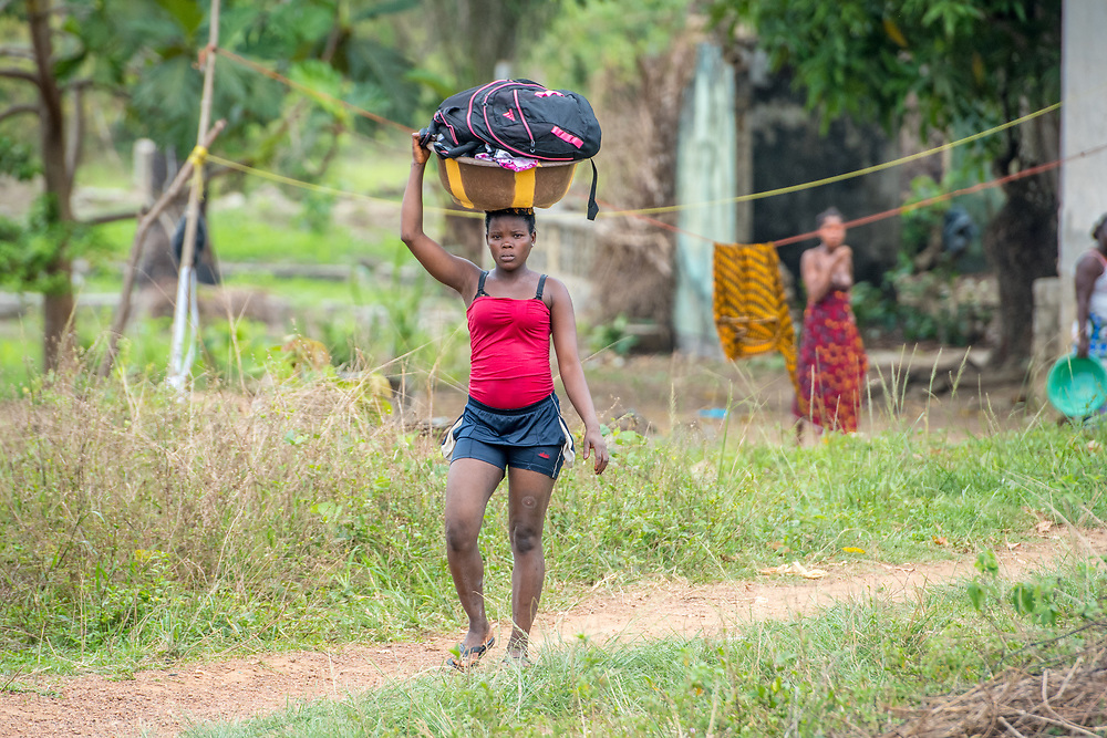 A woman carries a basket on her head in Ganta, Liberia