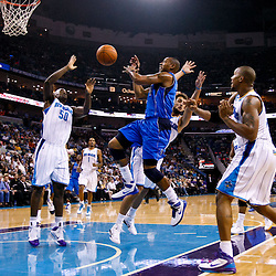 November 17, 2010; New Orleans, LA, USA; Dallas Mavericks small forward Caron Butler (4) passes between  New Orleans Hornets defenders during the first quarter at the New Orleans Arena. Mandatory Credit: Derick E. Hingle