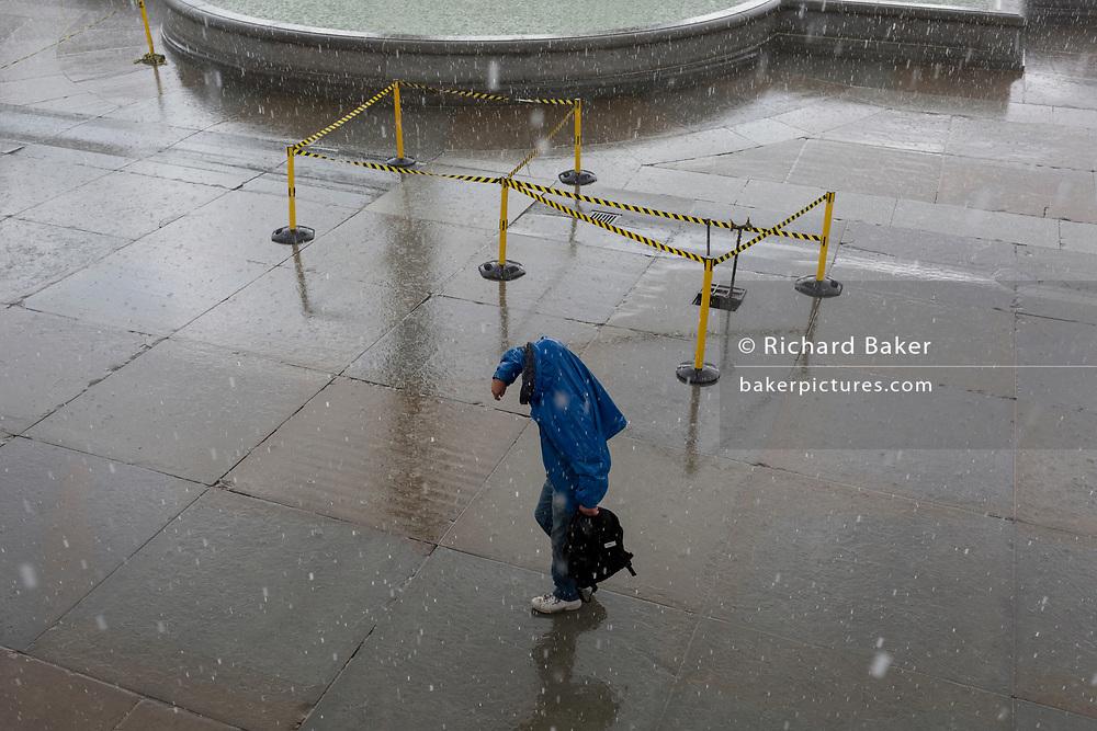 A man struggles through sudden heavy rain in Trafalgar Square, on 13th August 2018, in London, England.