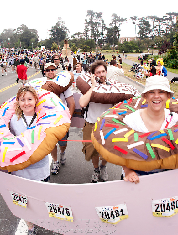 "Posing as a box of ""American doughnuts,"" San Franciscans Lauren Shimek, from left, husband Justin Shimek, Vincent Voelz and Kristi Kelly march through Golden Gate Park at the 97th running of the Bay to Breakers 12K race, Sunday, May 18, 2008 in San Francisco. (Photo by D. Ross Cameron)"