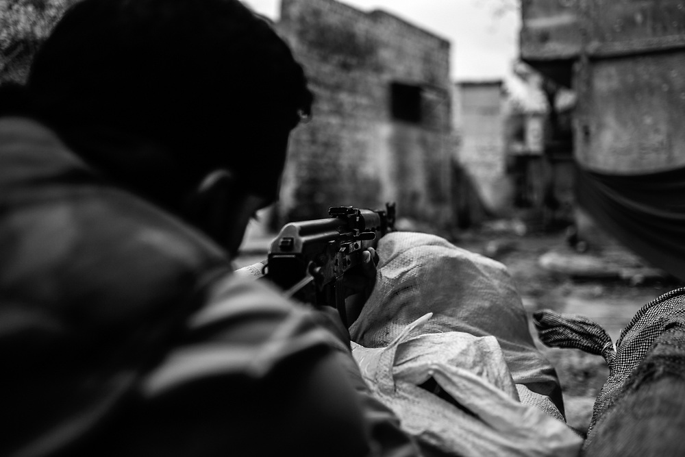 Aleppo, Syria, 2012/10/22.<br /> Karmal Jabal district.<br /> A FSA fighter checking with his Kalashnikov, the position of Al-Assad troops.