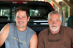 Father and son smiling on back of a parked truck