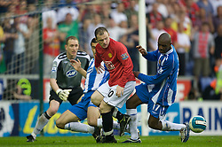 WIGAN, ENGLAND - Sunday, May 11, 2008: Manchester United's Wayne Rooney is tackled by Wigan Athletic's Emmerson Boyce during the final Premiership match of the season at the JJB Stadium. (Photo by David Rawcliffe/Propaganda)