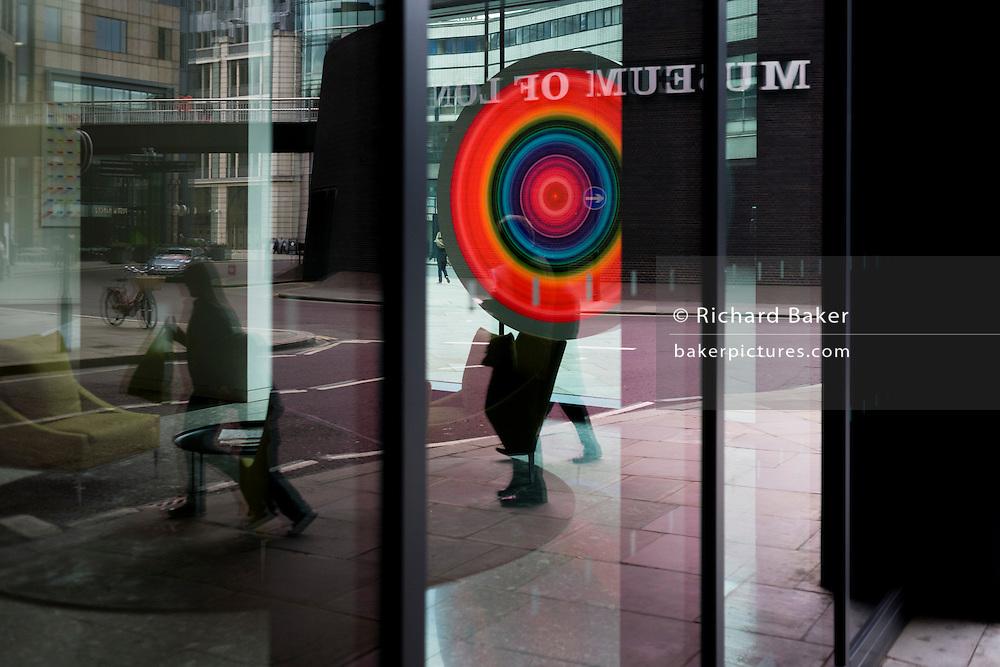 Circle artwork installation seen through reflective office foyer windows.