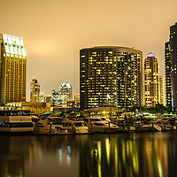 Photo of San Diego skyline at night with luxury yachts at Embarcadero Marina with downtown San Diego buildings. Photo is high resolution and was taken in 2012.