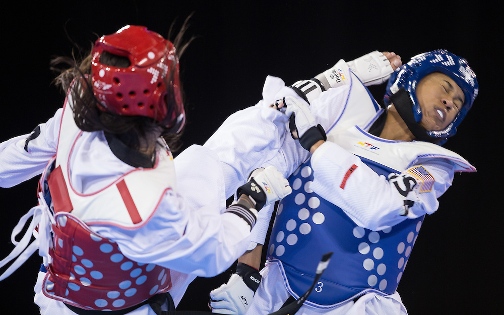 Paige McPherson (R) of the United States tries to avoid a kick to the head from Julia Vasconcelos of Brazil during their semi-final contest in women's taekwondo -67 kg division at the 2015 Pan American Games in Toronto, Canada, July 21,  2015.  AFP PHOTO/GEOFF ROBINS
