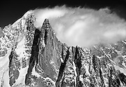 An aerial photograph of the Aiguille Verte and the Petite Drus with blowing clouds, a dramatic part of the Massif of Mont Blanc, above the valley of Chamonix in France.