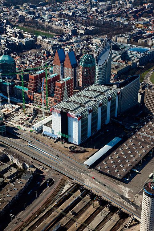 Nederland, Zuid-Holland, Den Haag, 20-03-2009; het ministerie van VROM naast de overkapping en sporen van Den Haag Centraal. Naast VROM bouwkranen van de JuBi-bouwput (gecombineerd ministerie Justitie en Binnenlandse zaken). Ministerie VWS in de dubbele torens (de Haagse tieten), daarnaast Zurichtoren (o.a OPTA en NMA), in de Hoftoren (afgeschuind) ministerie OCenW./ Achter de hoogbouw het Plein, Hofvijver. View on The Hague. Next to the roofing and rails of the Central Station (r) the Ministry of Housing. The blue roofed twin buildings are called The Tits of The Hague, residence of the Ministry of Health. Behind the high rise the Court Pond (Hofvijver)..Swart collectie, luchtfoto (toeslag); Swart Collection, aerial photo (additional fee required)