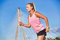Portrait of young attractive woman running in park