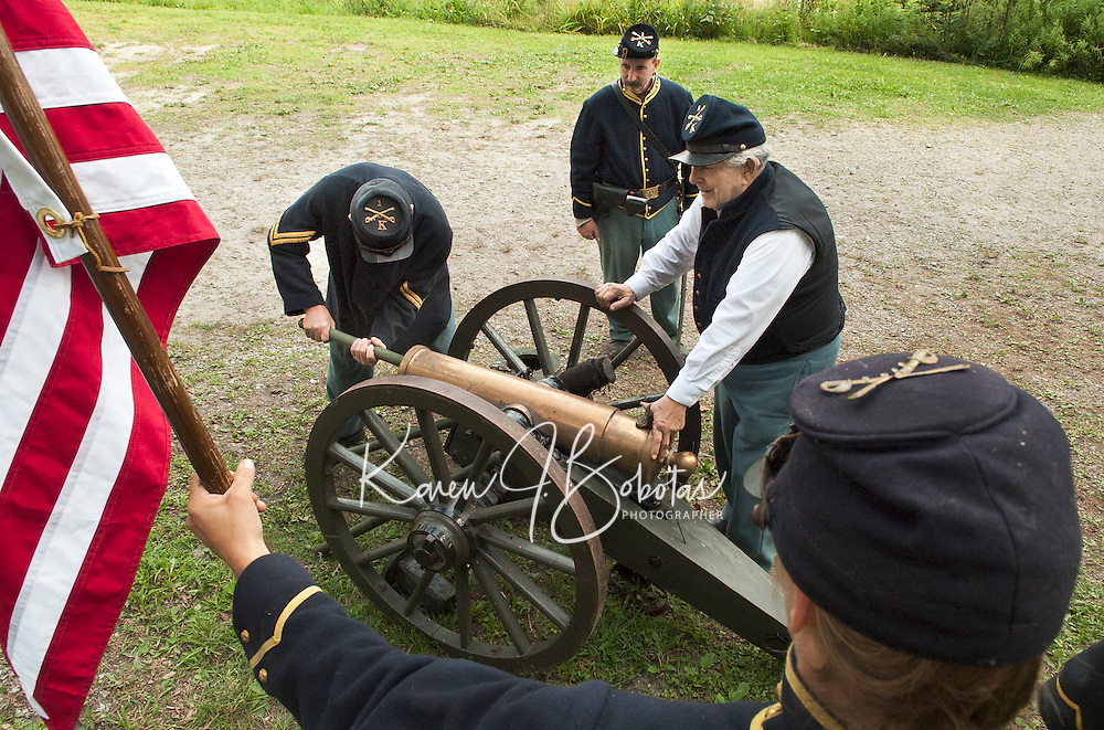 Corporal Larry Gilman rams the charge with Bob Duffy and Private Howard Leonard preparing for the cannon blast as Kelly Hoyt holds the American flag during the Civil War encampment at the NH Veterans Association compound off Lakeside Avenue in the Weirs Sunday morning.  (Karen Bobotas/for the Laconia Daily Sun)
