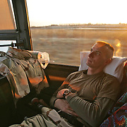 As the sun rises, a member of the Iowa National Guard 224th Batallion, is lost in thought as he returns home to Iowa by bus from ft. Sill, Ok., at the end of an all night trip.   His unit spent a week of demobilization at Ft. Sill, a process that left the soldiers weary, especially after spending the past year in Iraq.  Many soldiers who return from Iraq find the adjustment difficult, often experiencing marital problems and challenges assimilating  back into society.  The reunion for the 224th was in Fairfield, Iowa.
