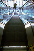 Silhouette of a man at the bottom of an escalator