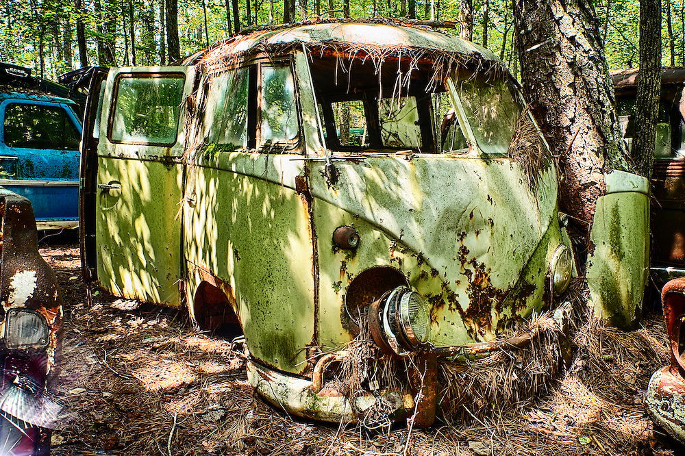 An old green van is slowly rusting away in the middle of the Old Car City junkyard in Georgia.