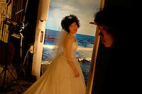 """A woman waiting to have her wedding pictures taken at """"New-York, New-York Studios"""" in central Beijing. September 2005."""