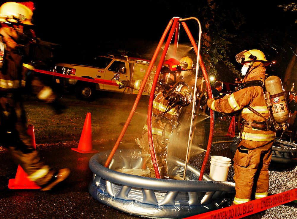 Edmonton, AB - August 28/08 - A firefighter gets decontaminated after fighting a house fire at 112ave and 69st around midnight on August 28.   No word on the cause.  Photo by Daniel Hayduk