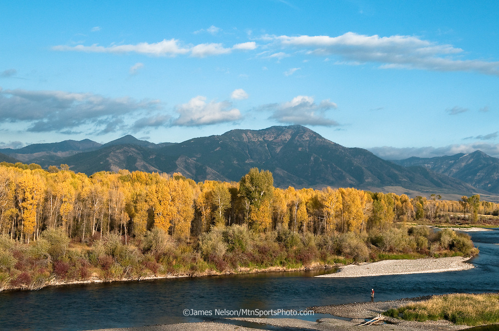 An angler fly fishes for trout during an autumn afternoon on the South Fork of the Snake River, Idaho.