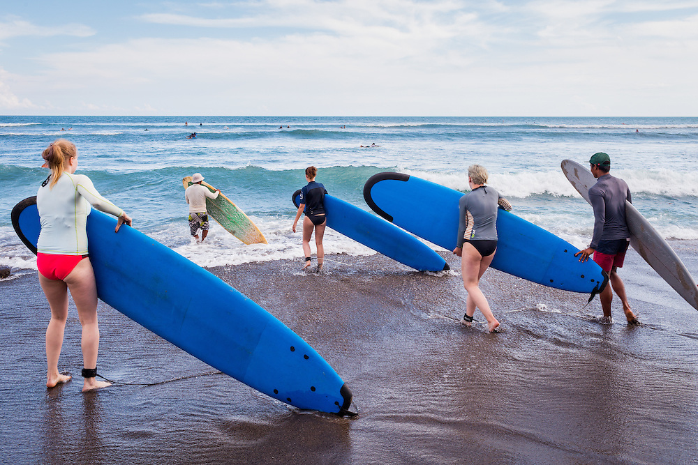 Surfers carry their surfboards at Batubolong beach in Canggu.