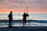 Southeast Asia, Thailand, Koh Chang Silhouette of Local fishermen on the beach at sunset