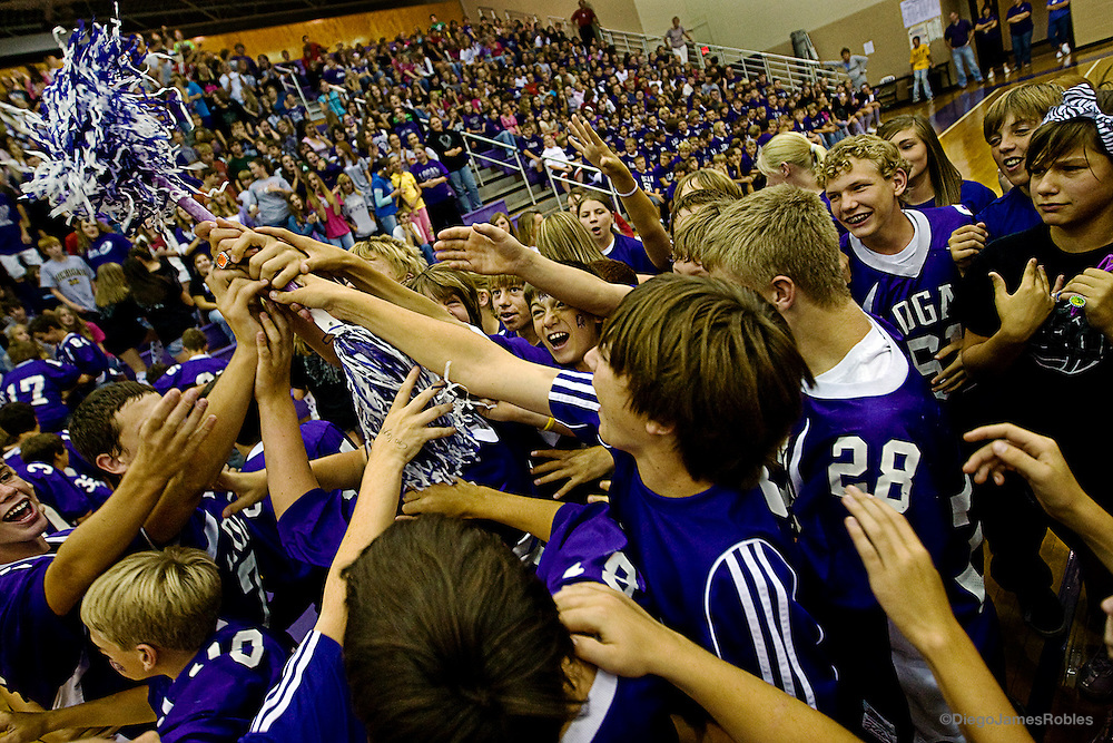Pre-teens from Chieftain Elementary School struggle to touch the Chieftain Baton during a pep rally in honor of the Chieftains football team.