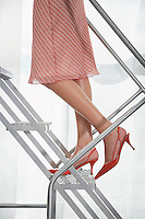 Young woman wearing high heeled shoes ascending aluminium staircase low section side view