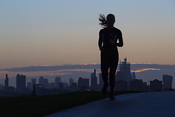 A runner cuts through the horizon as day breaks over London's skyline, seen from Primrose Hill, to the north of the city. London, November 13 2018.