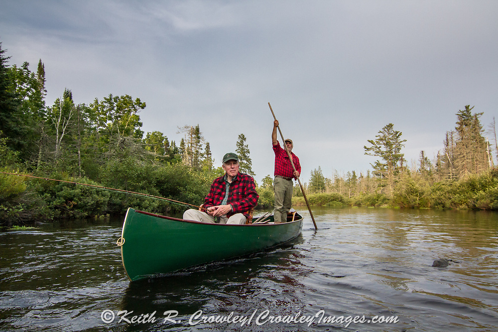 Brule River fishing guide Damian Wilmot poles upstream on the Brule with angler Matson Holbrook in a 1895 Joe Lucius guide canoe Wilmot meticulously restored over the course of two years.