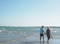 Senior couple walking on beach back view